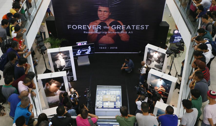 """Filipino fans look at  memorabilia from the """"Thrilla in Manila"""" World Heavyweight boxing fight between Muhammad Ali and Joe Frazier at the launch of an exhibit at The Ali Mall in suburban Quezon city northeast of Manila, Philippines to pay tribute to Muhammad Ali who died exactly a week ago Friday, June 10, 2016. The fight was dubbed the """"Most Legendary Fight in History"""". (AP Photo/Bullit Marquez)"""