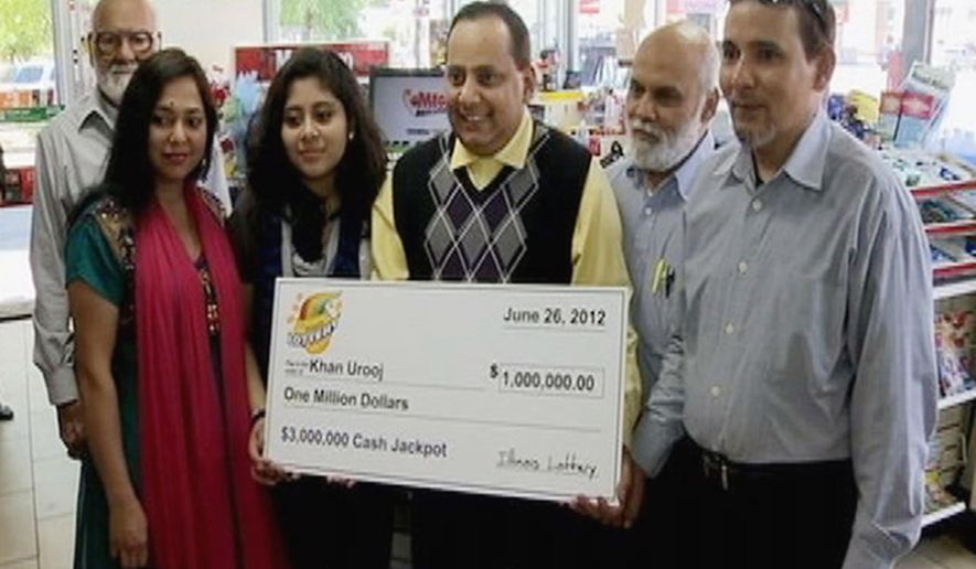 FILE - This June 2012 file photo provided by WMAQ-TV in Chicago, shows Urooj Khan, center, holding a ceremonial check in Chicago for $1 million as winner of an Illinois instant lottery game. At left, is Khan's wife, Shabana Ansari. Khan died suddenly on July 20, 2012, just days before he was to collect his winnings. With his departure from office this week, Stephen Cina, the former Cook County medical examiner leaves behind a beguiling mystery that he set in motion with a sensational declaration three years ago that Khan was poisoned with cyanide. (Courtesy of WMAQ-TV in Chicago via AP, File)