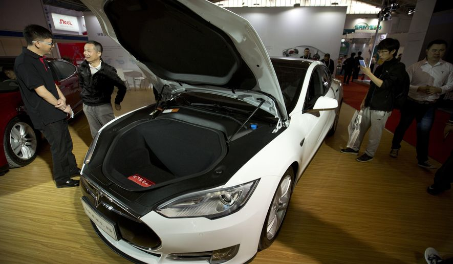 FILE - In this Monday, April 25, 2016, file photo, visitors gather around a Tesla Model S electric car on display at the Beijing International Automotive Exhibition in Beijing. Tesla Motors is denying allegations that there are safety problems with its vehicle suspensions. The Palo Alto, Calif., company says one of its cars had an abnormal amount of rust on a suspension part, a problem it hasn't seen in any other car. (AP Photo/Mark Schiefelbein, File)