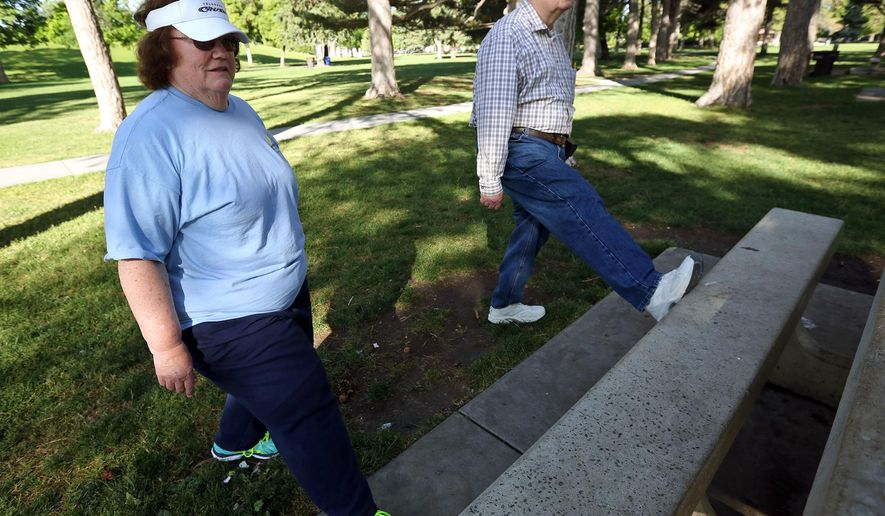 In this June 1, 2016, photo, Pat Wilson and Les Wilson stretch before walking around Liberty Park in Salt Lake City. Walking is helping groups of retirees beat the aches and pains that have set in over time: creaking joints, tender knees, fatigue, malaise and arthritis. (Kristin Murphy/The Deseret News via AP)  SALT LAKE TRIBUNE OUT; MAGS OUT; MANDATORY CREDIT; TV OUT