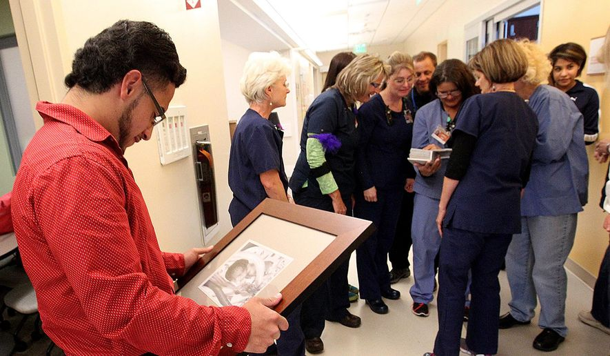 Rosalio Garcia looks at a picture of himself which hangs on a wall in the Neonatal Intensive Care Unit at St. Mary's Hospital in Grand Junction, Colorado, during a visit to the unit on April 25, 2016. Meanwhile,  some of the nurses who took care of him 18 years ago look at a photo album he brought with him. (Dean Humphrey/The Grand Junction Daily Sentinel via AP) ** FILE **