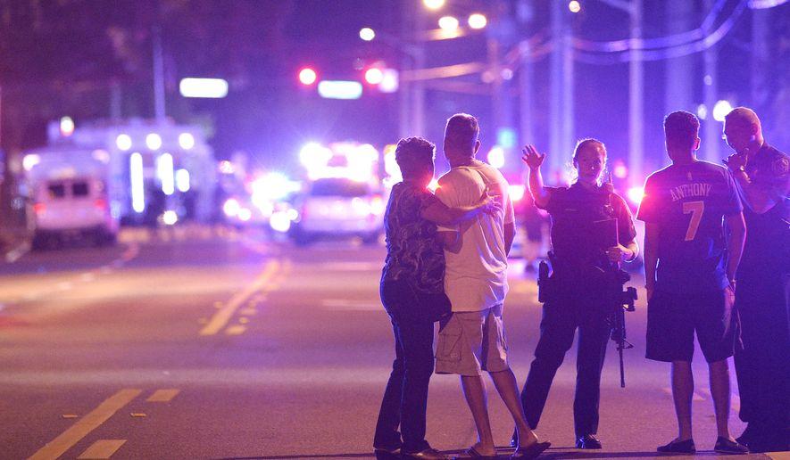Orlando Police officers direct family members away from a fatal shooting at Pulse Orlando nightclub in Orlando, Fla., Sunday, June 12, 2016. (AP Photo/Phelan M. Ebenhack)