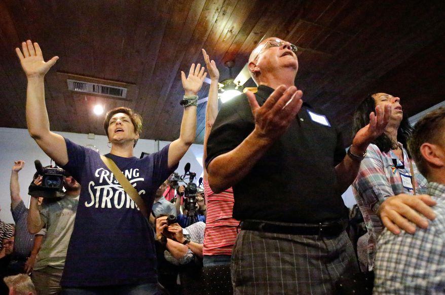 Parishioners pray for the victims of a nightclub shooting involving multiple fatalities, during a vigil at the Joy Metropolitan Community Church in Orlando, Fla., Sunday, June 12, 2016. (AP Photo/John Raoux)