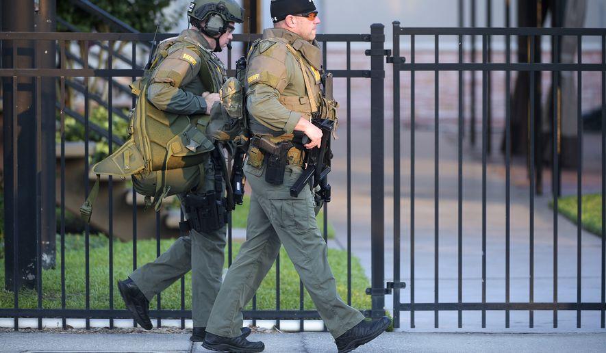 Orange County Sheriff's Department SWAT members arrive to a fatal shooting at Pulse Orlando nightclub in Orlando, Fla., Sunday, June 12, 2016. (AP Photo/Phelan M. Ebenhack)
