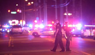 Police officers stand guard down the street from the scene of a shooting involving multiple fatalities at a nightclub in Orlando, Fla., Sunday, June 12, 2016. (AP Photo/Phelan M. Ebenhack)