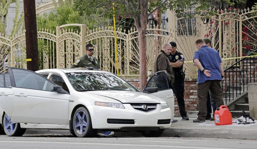 Investigators view items removed from a car, left, after a heavily armed man was arrested in Santa Monica, Calif., early Sunday, June 12, 2016. The man reportedly told police he was in the area for West Hollywood's huge gay pride parade. Authorities did not know of any connection between the gay nightclub shooting in Orlando, Fla., early Sunday and the Santa Monica arrest. (AP Photo/Reed Saxon)