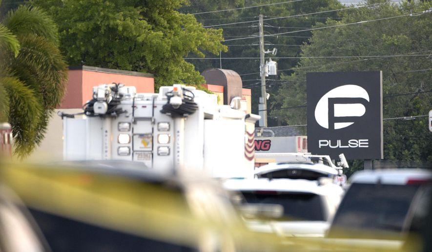 Police cars and emergency vehicles surround the Pulse Orlando nightclub, the scene of a fatal shooting, in Orlando, Fla., Sunday, June 12, 2016. (AP Photo/Phelan M. Ebenhack)