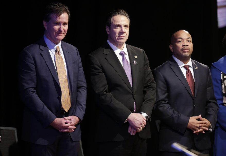 FILE - In this Jan. 13, 2016, file photo, New York Gov. Andrew Cuomo, center, stands with Senate Majority Leader John Flanagan, left, R-Smithtown, and Assembly Speaker Carl Heastie, D-Bronx, before delivering his State of the State address and executive budget proposal at the Empire State Plaza Convention Center in Albany, N.Y. Another legislative session is drawing to a close and New York state lawmakers are no closer to addressing government ethics. Cuomo has proposed ideas including tighter campaign finance laws and limits on lawmaker's outside pay, but those have failed to get traction with lawmakers. (AP Photo/Mike Groll, File)