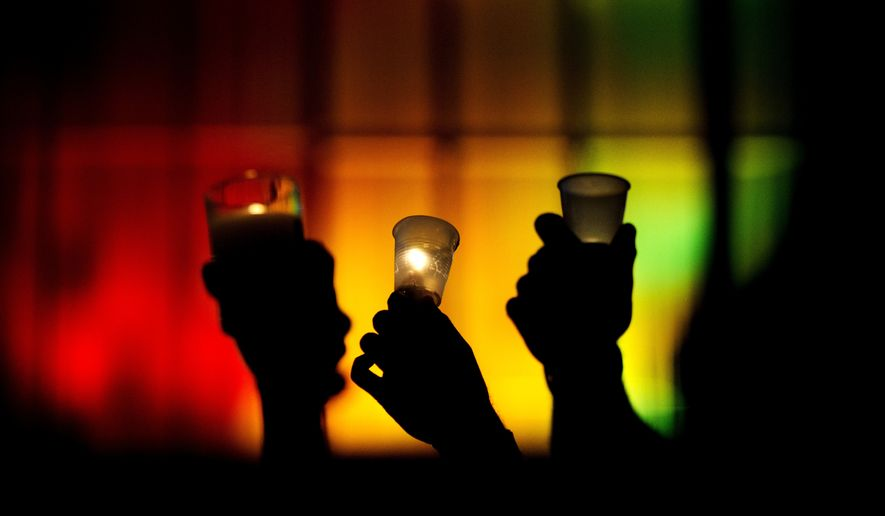 People hold up candles against a rainbow lit backdrop during a vigil for those killed in a mass shooting at the Pulse nightclub downtown Monday, June 13, 2016, in Orlando, Fla. (AP Photo/David Goldman)