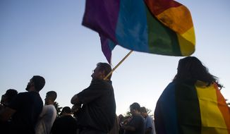 Alex Oliphant holds a rainbow flag outside Phoenix Pride during a vigil for the victims of the Orlando shooting on June 12, 2016 in Phoenix, Ariz.(Patrick Breen/The Arizona Republic via AP)