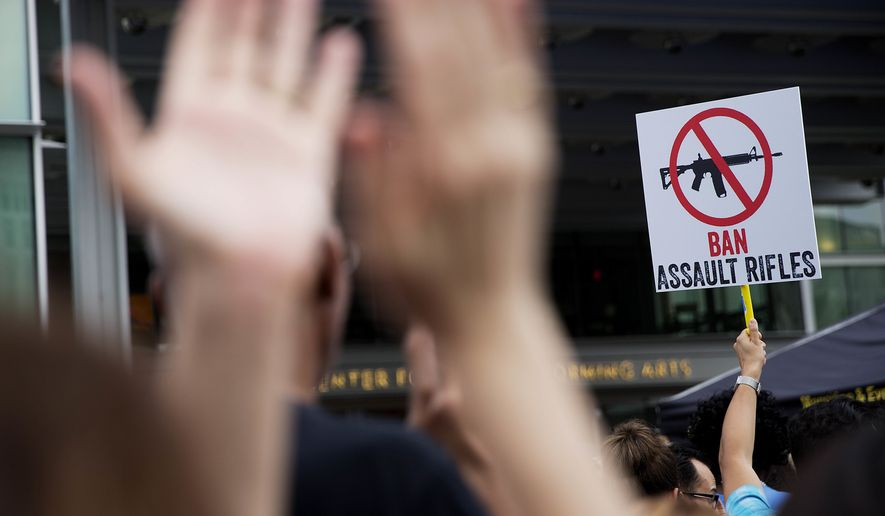 A crowd member holds up a sign as audience members applaud during a speech at a vigil downtown for those killed in a mass shooting at the Pulse nightclub Monday, June 13, 2016, in Orlando, Fla. (AP Photo/David Goldman)