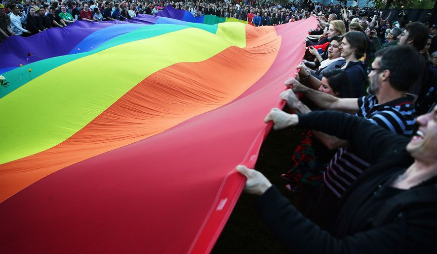 People wave a large rainbow flag during a vigil in Seattle for the victims of a mass shooting at Pulse nightclub in Orlando, Fla., Sunday, June 12, 2016. (Genna Martin/seattlepi.com via AP) MAGS OUT; NO SALES; SEATTLE TIMES OUT; TV OUT; MANDATORY CREDIT
