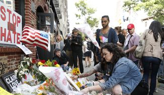 Giovanna Lopez, who says she knew several victims of the Orlando nightclub shootings, lays flowers for her friends at the historic Stonewall Inn, Monday, June 13, 2016, in New York. (AP Photo/Kathy Willens)