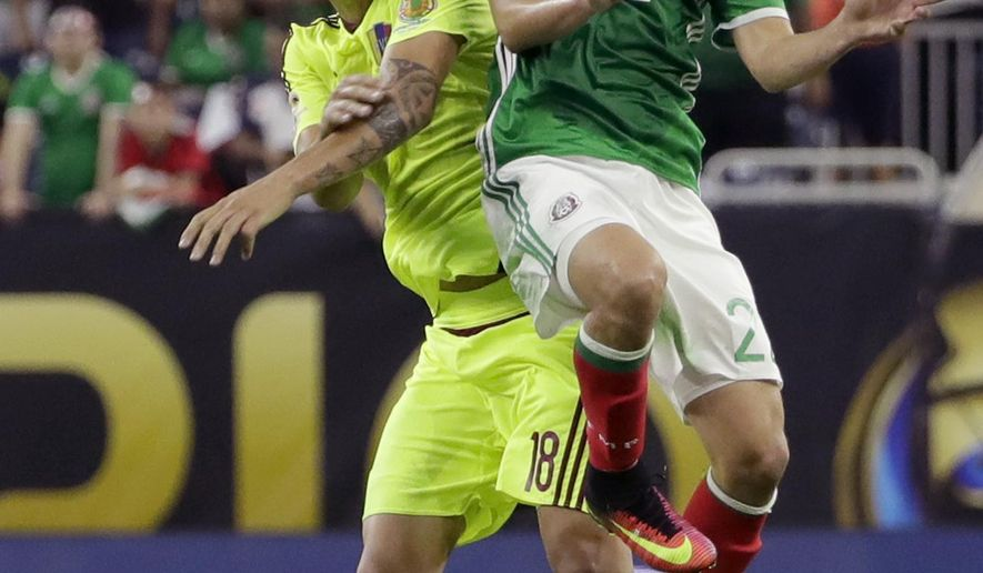 Venezuela midfielder Adalberto Penaranta (18) and Mexico defender Paul Aguilar (22) try to head the ball during a Copa America Centenario group C soccer match, Monday, June 13, 2016, in Houston. (AP Photo/David J. Phillip)