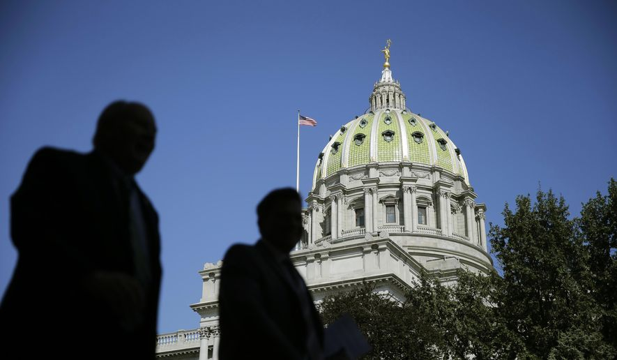 In this Oct. 7, 2015 photo, people walk past the Pennsylvania Capitol building in Harrisburg, Pa. (AP Photo/Matt Rourke)