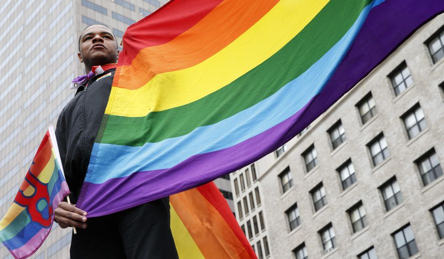 Sam Johnson, of Boston, holds a rainbow flag during a vigil on City Hall Plaza for the victims in the Orlando nightclub attack, Monday, June 13, 2016, in Boston. (AP Photo/Michael Dwyer)