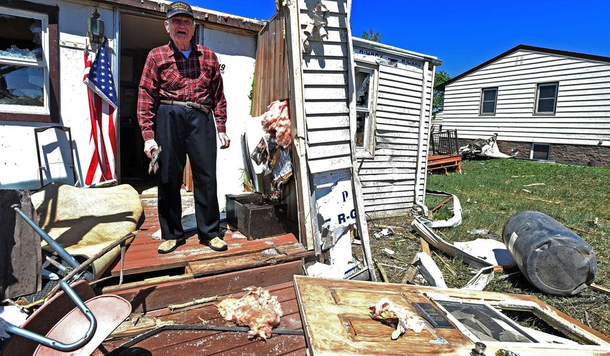 In this June 12, 2016 photo, Fritz Goernet, a World War II veteran, stands on what remains of his front porch and surveys the damage done by a tornado that swept through the town of Baker, Mont., Saturday evening. Baker Rural Fire Department Chief Tom Bruha says the storm severely damaged more than 30 homes and completely destroyed a half dozen. (Hannah Potes/Billings Gazette via AP)