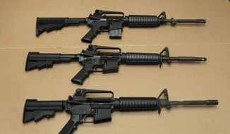 In this Aug. 15, 2012, file photo, three variations of the AR-15 assault rifle are displayed at the California Department of Justice in Sacramento, Calif. While the guns look similar, the bottom version is illegal in California because of its quick reload capabilities. Omar Mateen used an AR-15 that he purchased legally when he killed 49 people in an Orlando nightclub over the weekend. (AP Photo/Rich Pedroncelli,file)