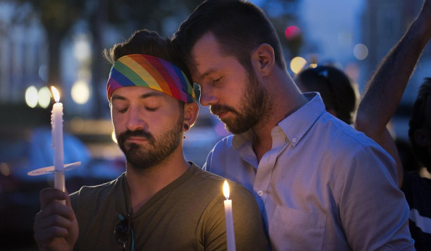 Eddie Desormeau, left, is consoled by Mike Post, right while holding candles during a moment of silence during a candlelight vigil mourning the victims of the Orlando night club attack on Sunday, June 12, 2016, at the Apartment Lounge bar in Grand Rapids, Mich.  (Tom Brenner/The Grand Rapids Press-MLive.com via AP)