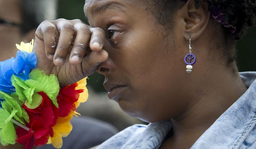 Shaniqua Evans, 29, of Washington, cries during a vigil in Washington, Monday June 13, 2016, hosted by the Muslim American Women's Policy Forum, in memory of the victims of the Orlando mass shooting. A gunman opened fire inside a crowded gay nightclub early Sunday, before dying in a gunfight with SWAT officers, police said. (AP Photo/Cliff Owen)