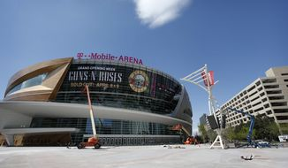 In this March 28, 2016, photo, workers finish construction outside of the T-Mobile Arena in Las Vegas. The latest multi-million dollar development on the Las Vegas Strip features a leafy outdoor pedestrian area, 20,000 seat arena and small theater. The arena is scheduled to open April 6. (AP Photo/John Locher)