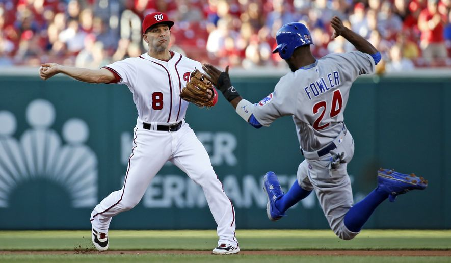 Washington Nationals shortstop Danny Espinosa (8) gets the out at second base on Chicago Cubs' Dexter Fowler (24), and throws to first for the out on Jason Heyward for a double play during the first inning of a baseball game at Nationals Park, Tuesday, June 14, 2016, in Washington. (AP Photo/Alex Brandon)