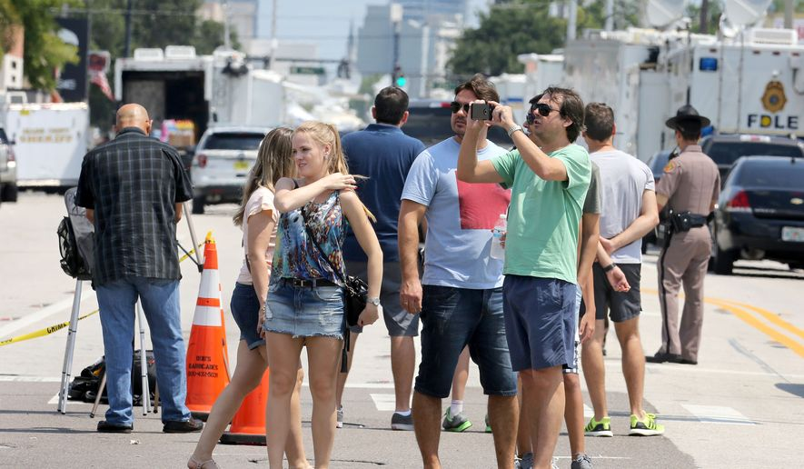 Tourists survey the scene near the Pulse nightclub in Orlando, Fla., Tuesday, June 14, 2016, site of a mass shooting on Sunday.   (Joe Burbank/Orlando Sentinel via AP)