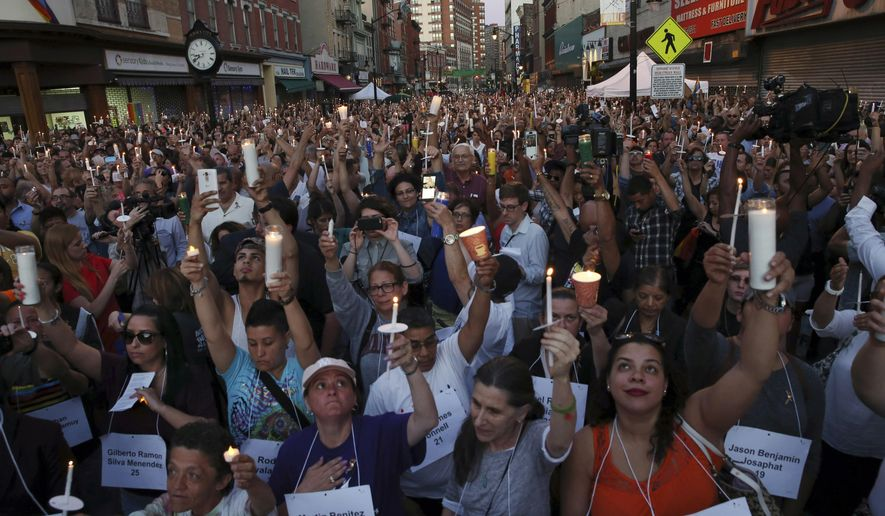 People hold candles in the air as a large crowd gathers to pay their respects for the the victims and survivors of the Orlando nightclub shooting Tuesday, June 14, 2016, in Jersey City, N.J. A gunman killed dozens of people in a massacre at a crowded gay nightclub in Orlando, Fla., on Sunday, making it the deadliest mass shooting in modern U.S. history. (AP Photo/Mel Evans)