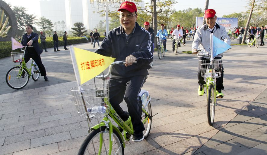 In this Thursday Jan. 01, 2015, photo, Liu Xiaohua, center, deputy secretary general of the Guangdong Communist Party committee rides a rental bike with officials after launching the rental bike system in Zhanjiang, southern China's Guangdong province. Liu, a leading official in China's southern manufacturing powerhouse of Guangdong province has been found dead in an apparent suicide, state media said Tuesday, June 14, 2016, underscoring the extreme pressure some local leaders are under over job stress and an ongoing crackdown on corruption. (Chinatopix via AP) CHINA OUT
