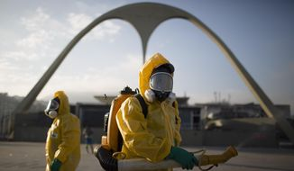 In this Tuesday, Jan. 26, 2016, file photo, a health workers stands in the Sambadrome spraying insecticide to combat the Aedes aegypti mosquito that transmits the Zika virus in Rio de Janeiro, Brazil. (AP Photo/Leo Correa, File)