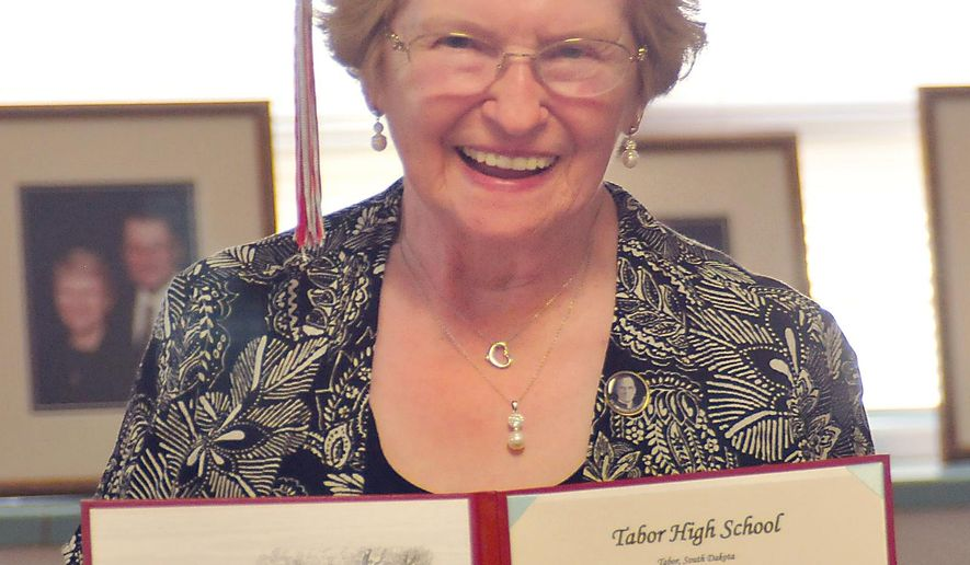 Darlene Carda beams with pride as she shows off her honorary diploma as a member of the Tabor High School Class of 1953, Monday, June 13, 2016. Carda never completed high school as she married her husband before he entered the Korean War. She received her diploma Monday night during the Bon Homme school board meeting.  (Randy Dockendorf/Yankton Press & Dakotan via AP) MANDATORY CREDIT