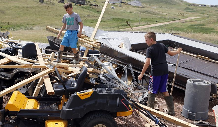 Cooper Hill, left, and Reno Lowe look through what is left of Chris Lowe's shop building roughly 8 miles northeast of Hermosa, S.D., Tuesday morning, June 14, 2016, after a tornado ripped through it the night before. National Weather Service reports show the twister hit about 4:30 p.m. Monday, causing structural damage to several homes. (Chris Huber/Rapid City Journal via AP) TV OUT; MANDATORY CREDIT
