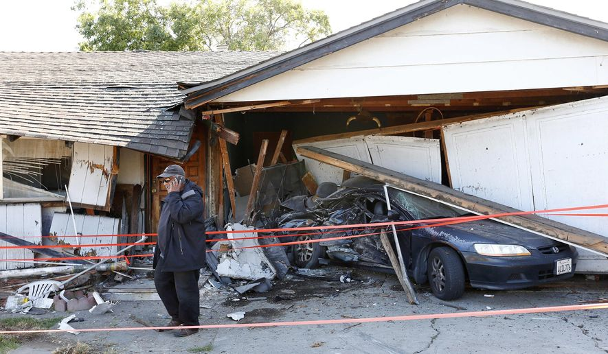 Ray Minter talks on the phone after a truck ran into his home near Interstate 680 in San Jose, Calif., Tuesday, June 14, 2016. Minter said he has lived there since 1960. (Gary Reyes/San Jose Mercury News via AP) MANDATORY CREDIT