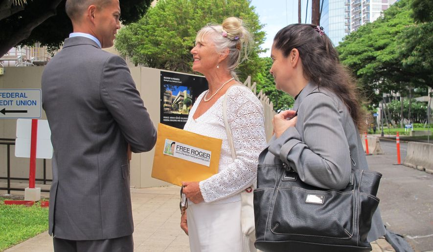 This Sept. 27, 2013 file photo shows Sherryanne Christie, center, wife of Hawaii Cannabis Ministry founder Roger Christie, talking to her husband's attorney, Thomas Otake, left, and her attorney, Lynn Panagakos, outside federal court in Honolulu. A federal appeals court has upheld the convictions of two Hawaii Cannabis Ministry leaders found guilty of having 300 pot plants as part of a distribution ring.(AP Photo/Audrey McAvoy)