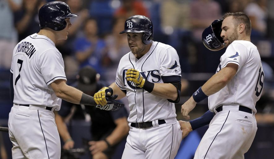 Tampa Bay Rays' Evan Longoria, center, celebrates with Curt Casali, right, and Logan Morrison, left, after his three-run home run off Seattle Mariners relief pitcher Nick Vincent during the seventh inning of a baseball game Tuesday, June 14, 2016, in St. Petersburg, Fla. (AP Photo/Chris O'Meara)