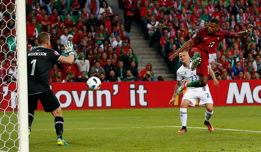 Portugal's Nani, right, challenges Iceland goalkeeper Hannes Halldorsson, left, during the Euro 2016 Group F soccer match between Portugal and Iceland at the Geoffroy Guichard stadium in Saint-Etienne, France, Tuesday, June 14, 2016. (AP Photo/Pavel Golovkin)