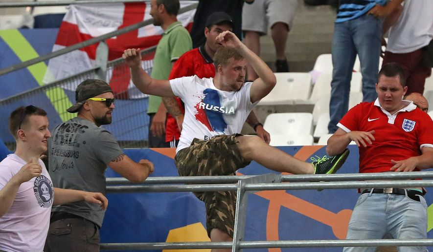 FILE - In this Saturday, June 11, 2016 file photo, Russian supporters attack an England fan at the end of the Euro 2016 Group B soccer match between England and Russia, at the Velodrome stadium in Marseille, France. UEFA's disciplinary body says Tuesday, June 14, 2016 Russia will be disqualified from the European Championship if there is more fan violence inside stadiums in France. (AP Photo/Thanassis Stavrakis, File)