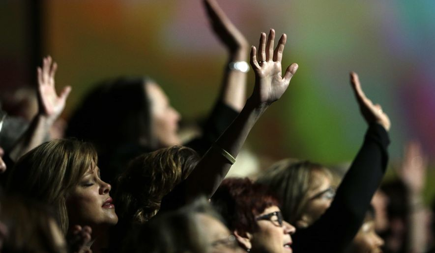 Members of the choir raise their arms as they worship during a meeting of the Southern Baptist Convention Tuesday, June 14, 2016, in St. Louis. (AP Photo/Jeff Roberson)