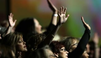 Members of the choir raise their arms as they worship during a meeting of the Southern Baptist Convention Tuesday, June 14, 2016, in St. Louis. (AP Photo/Jeff Roberson) ** FILE **