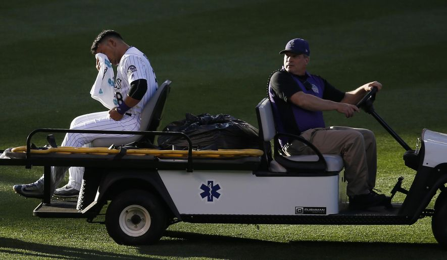 Colorado Rockies left fielder Gerardo Parra is carted off the field after injuring his left leg in a collision with shortstop Trevor Story while pursuing a fly ball off the bat of New York Yankees center fielder Jacoby Ellsbury in the top of the third inning of a baseball game Tuesday, June 14, 2016, in Denver. (AP Photo/David Zalubowski)