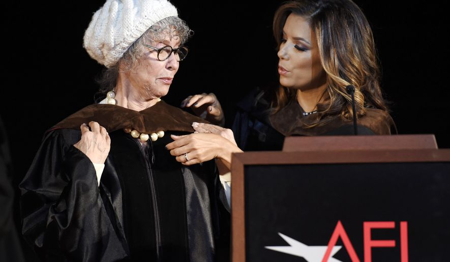 Speaker Eva Longoria, right, puts a hood on honoree Rita Moreno during the 2016 AFI Conservatory Commencement at the TCL Chinese Theatre on Wednesday, June 15, 2016, in Los Angeles. (Photo by Chris Pizzello/Invision/AP)