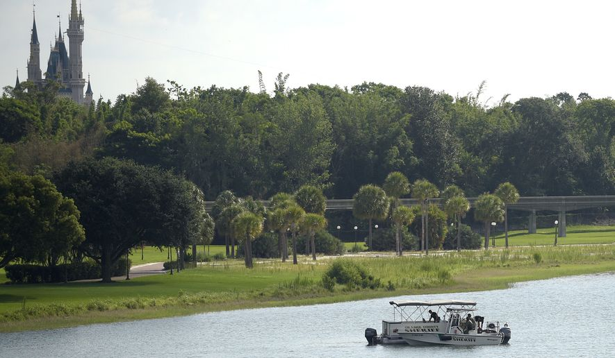 Orange County Sheriff's officers search the Seven Seas Lagoon between Walt Disney World's Magic Kingdom theme park, left, and the Grand Floridian Resort & Spa on Wednesday in Lake Buena Vista, Fla., after a two-year-old toddler was dragged into the lake by an alligator. (Associated Press)