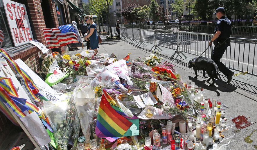 A counterterrorism officer walks his bomb-sniffing dog past a makeshift memorial for victims of the Orlando nightclub shooting in front of the Stonewall Inn, the birthplace of the modern gay rights movement, Wednesday, June 15, 2016, in New York. (AP Photo/Kathy Willens)