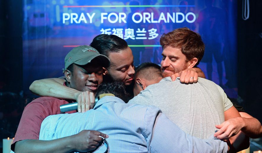 People embrace during a memorial service for victims of the Orlando mass shooting in Shanghai, China, Tuesday, June 14, 2016. A gunman killed dozens of people in a massacre at a crowded gay nightclub in Orlando, Fla., on Sunday, making it the deadliest mass shooting in modern U.S. history. (Chinatopix via AP)