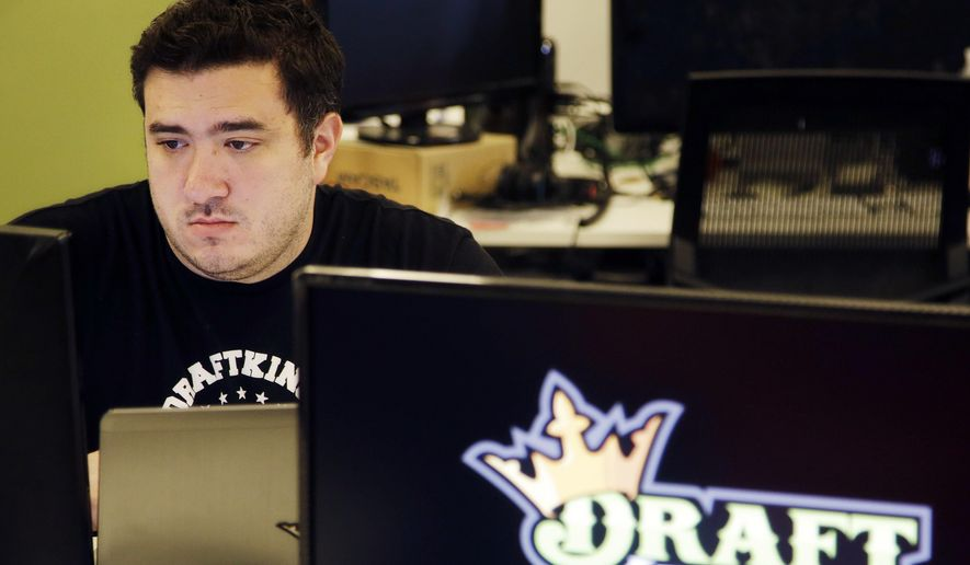 n this Sept. 9, 2015, file photo, Len Don Diego, marketing manager for content at the DraftKings daily fantasy sports company, works at his station at the company's offices in Boston. On June 19, 2017, the FTC put the merger on hold, citing federal antitrust concerns. (AP Photo/Stephan Savoia, File)