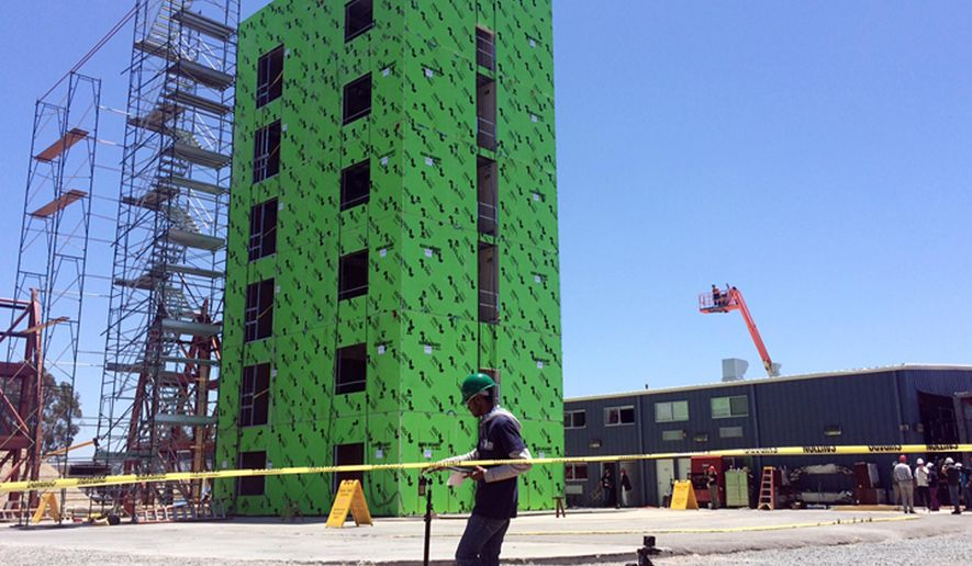 A researcher from the University of California, San Diego checks monitoring equipment in front of a six-story building that is undergoing a series of earthquake tests on a giant shake table, to see how the steel frame structure would fare in a major temblor, in San Diego Wednesday, June 15, 2016. (AP Photo/Julie Watson)