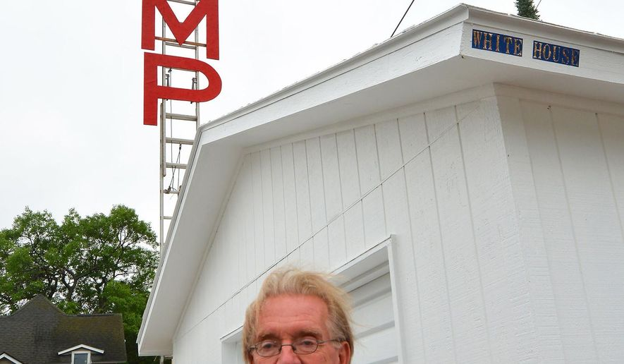 Michael Witte poses for a photo in the backyard of his home with a sign supporting Republican presidential candidate Donald Trump in Traverse City, Mich., Wednesday, June 15, 2016. Northern Michigan officials said the sign that rises roughly 35 feet above a garage roof is too big and high. (Dan Nielsen/Traverse City Record-Eagle via AP) MANDATORY CREDIT