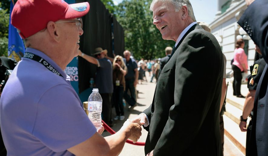 The Rev. Franklin Graham, right, shakes hands with a supporter before taking the stage at his rally the State Capitol in Madison, Wis., Wednesday, June 15, 2016. (Michael P. King/Wisconsin State Journal via AP) MANDATORY CREDIT