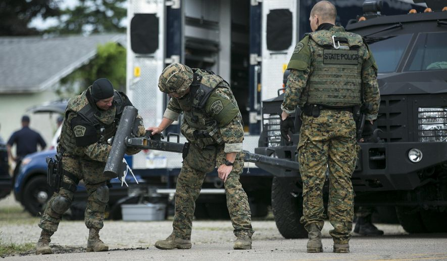 Michigan state police ES team members prepare their vehicle at a staging area nearby where a man with a gun has barricaded himself inside his home in Grand Junction, Mich while members of the Michigan State Police Emergency Reponse team urge him to come out on Tuesday, June 14, 2016. Sgt. David Caswell of the Michigan State Police Wayland post said roads in the area around County Road 681 and County Road 388 have been closed since the incident began late Tuesday morning. (Chelsea Purgahn/Kalamazoo Gazette via AP)