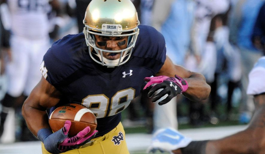 FILE - In this Oct. 11, 2014, file photo, Notre Dame wide receiver Corey Robinson makes a catch during an NCAA college football game against North Carolina in South Bend, Ind. Robinson has decided to walk away from football because of the lingering effects of a concussion, he said in a statement Wednesday, June 15, 2016. (AP Photo/Joe Raymond, File)